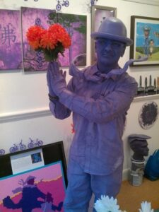 Purpleman holds orange flowers