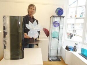 Terry holding Laura Heart lily next to cast glass sculpture by Fiaz Elson
