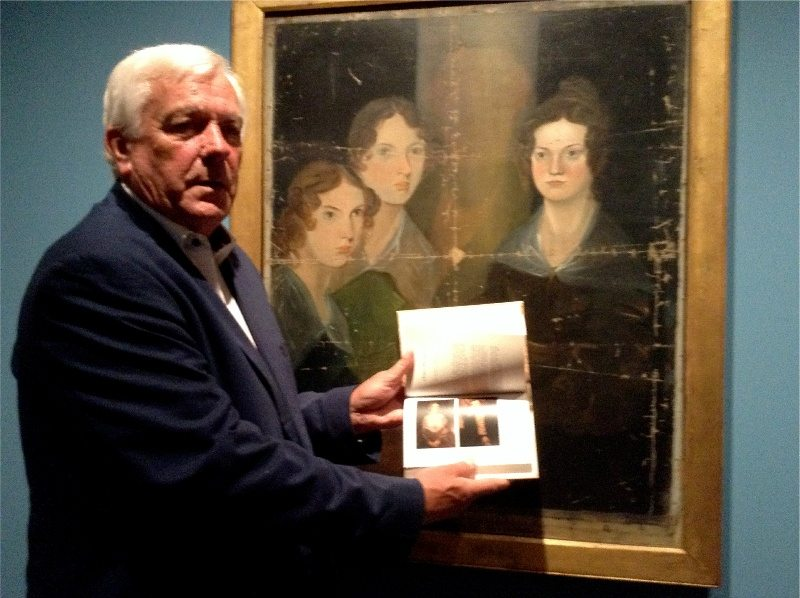 Author Alan Titterington holds a copy of his book in front of a painting by Bramwell Bronte